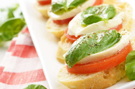 Caprese sandwiches of mozzarella tomato and basil closeup photo