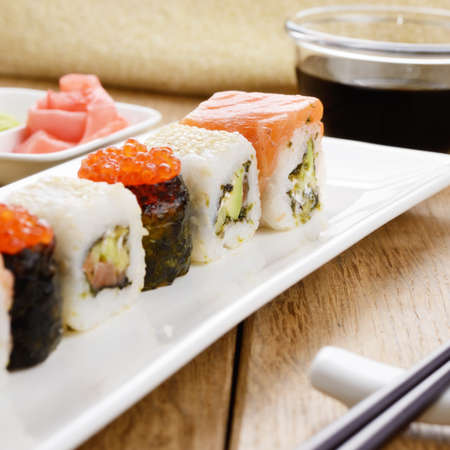 Mixed sushi on a white plate with soy sauce wasabi and ginger photo
