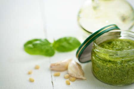pinoli: Vaso di vetro di salsa pesto sul tavolo da cucina bianco