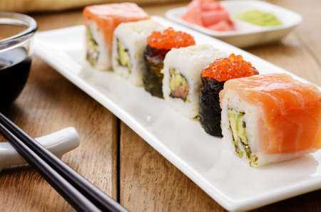 sushi roll: Mixed sushi set on a white plate with soy sauce wasabi and ginger Stock Photo