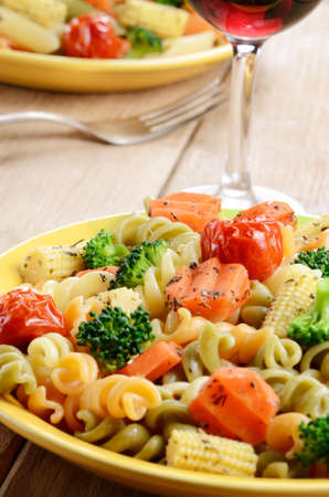Pasta fusilli salad with broccoli, carrot, corn, dried tomatoes on the kitchen table photo