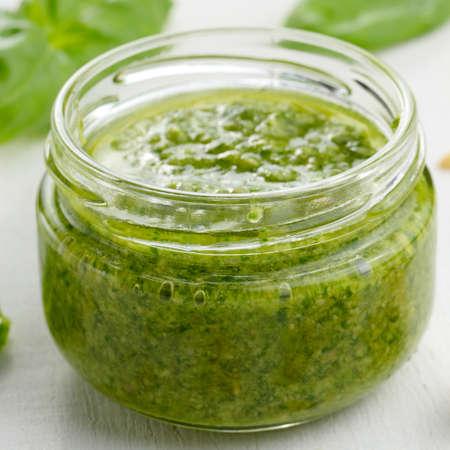 Glass jar of pesto sauce on white kitchen table closeup