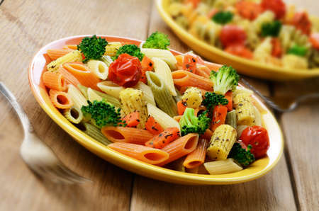 Pasta salad with broccoli carrot corn and dried tomatoes photo