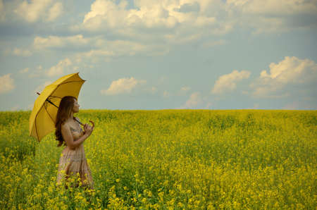 Young woman with umbrella at canola field photo