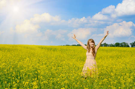 Young happy smiling woman having fun at canola field photo