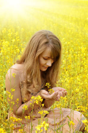 Young woman holds canola flower in arms photo