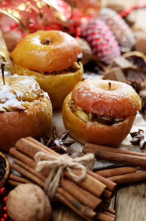Christmas background of homemade oven baked apples, spices, nuts, cons and decorations on wooden table photo
