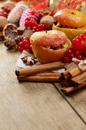 Christmas background of homemade oven baked apples, spices, nuts, cons and decorations on wooden table with copy-space photo