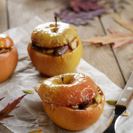 Homemade oven baked apples stuffed with cottage cheese, pumpkin seeds and almonds on baking paper. Fallen leaves used as autumn decor. Stock Photo