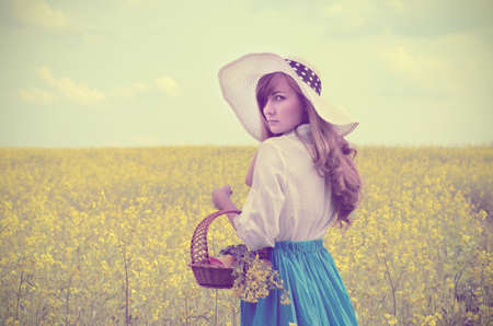 Young woman with basket having fun at canola field  Vintage style added photo
