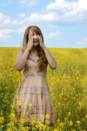 caucasian fever: Young woman sneezing at canola field suffering from hay fever or allergy Stock Photo