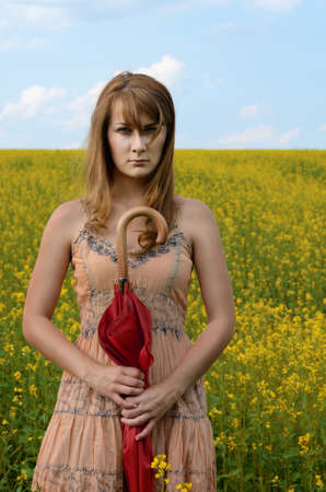 Young serious woman with red umbrella at canola field photo