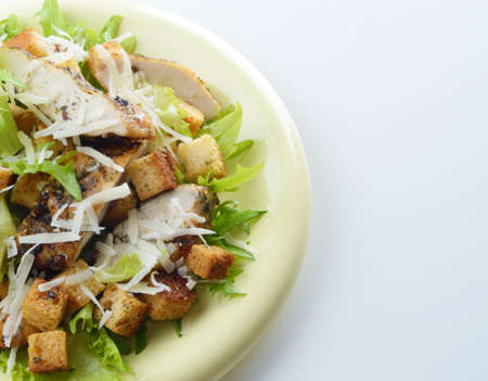 Caesar chicken salad with grated parmesan on white  photo