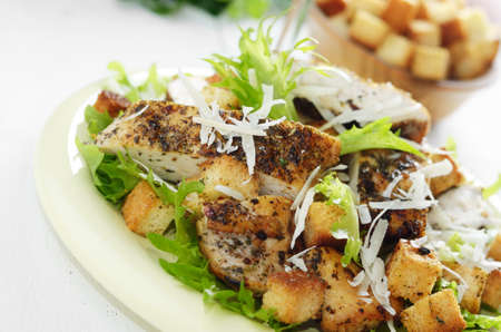 Caesar chicken salad with grated parmesan on white table photo