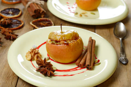 Christmas background of homemade oven baked apples stuffed with cottage cheese, pumpkin seeds and almonds served on plate photo
