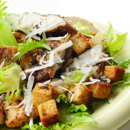 Caesar chicken salad with grated parmesan on white background photo