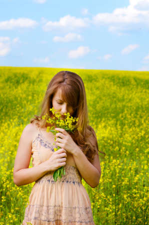 Young woman having fun at canola field with bouquet in arms photo