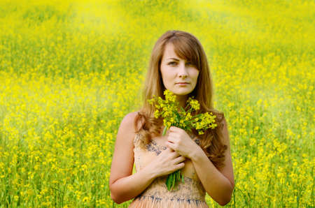 Young woman at canola field with bouquet in arms photo