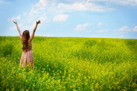 Young woman having fun at canola field photo