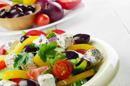 Homemade greek salad on white table photo