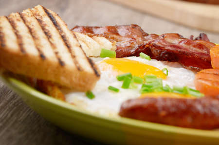 Fried eggs with bacon sausages and greens photo