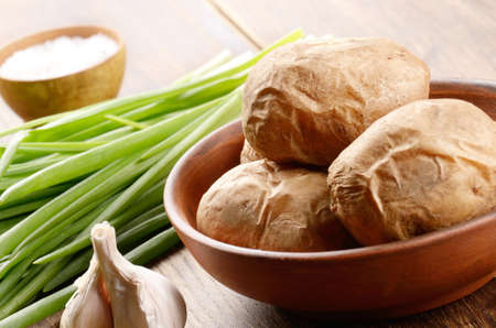 scallions: Dish with Baked potatoes with scallions on the wooden table
