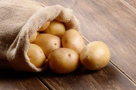 나무 테이블에 감자와 함께 삼 베 자루 스톡 콘텐츠