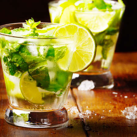Fresh cold lime mojito on wooden table
