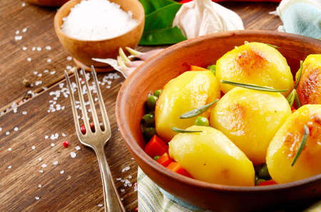 appetising: Boiled and baked potatoes with herbs and salt clay plate on wooden table