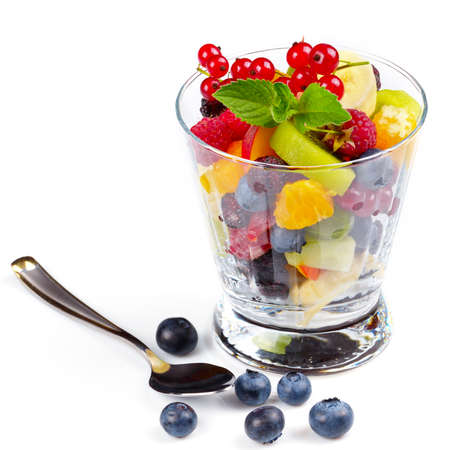 Fruit salad mix in glass on white background Stock Photo