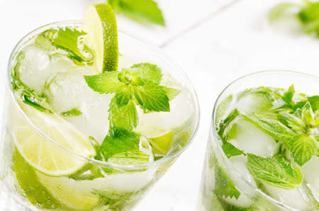Fresh cold lime mojito on white table