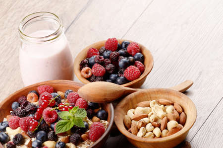 Oatmeal oats with berries nuts and yogurt on the wooden table Stock Photo