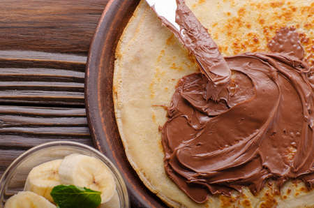 Flat lay French crepes with chocolate sauce and banana in clay bowl on wooden kitchen table