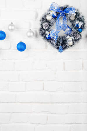 Christmas blue and silver balls and wreath on white brick wall holiday
