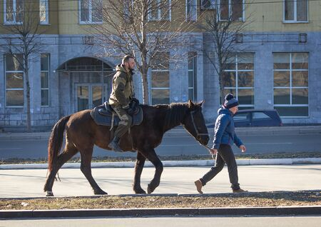 makeevka: Makeevka, Ukraine - February, 22, 2015: Boy ride a loshadisoldata Donetsk Peoples Republic during the holiday of Shrovetide
