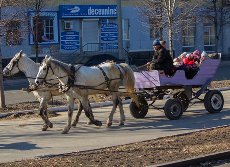 makeevka: Makeevka, Ukraine - February, 22, 2015: Children ride on a cart with horses during the holiday of Shrovetide