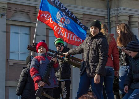 Makeevka, Ukraine - February, 22, 2015: The boy is photographed with a rifle under the flag of the Peoples Republic Donetskoy at the celebration of Shrovetide