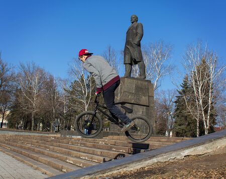 Makeevka, Ukraine - February, 22, 2015: Extreme stunts on the background of the monument to Lenin