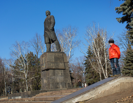 Makeevka, Ukraine - February, 22, 2015: The boy on the background of the monument to Vladimir Lenin in the central square