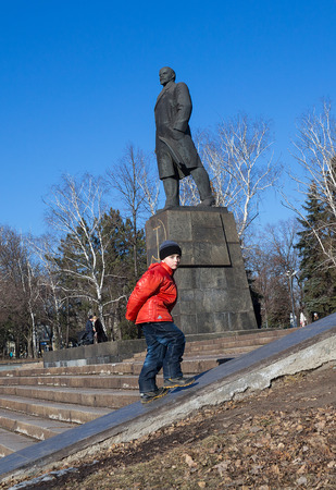 makeevka: Makeevka, Ukraine - February, 22, 2015: The boy on the background of the monument to Vladimir Lenin in the central square