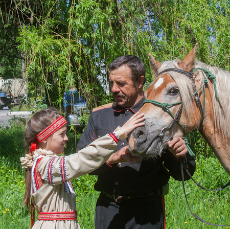 Makeevka, Ukraine - May, 7, 2014: Male cossack and a girl in national costume during the celebration of the anniversary of the victory over fascism
