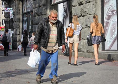 publicly: UKRAINE, KIEV - September 11,2013: Homeless man walking along the main street of the capital