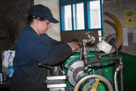 Ukraine, Anthracite - May 15, 2013: Woman-turner in the workplace. Antratsitovsky repair and engineering works. Lugansk region