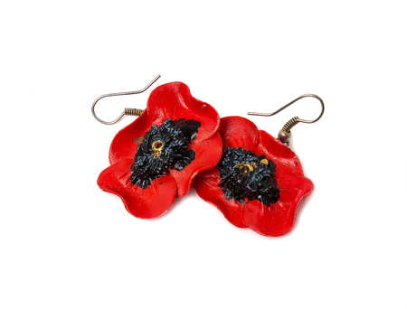 Earrings in the form of red poppies isolated on white photo