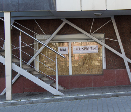 proclaimed: Donetsk, Ukraine - March, 25, 2015: Showcase in the city center. Closed plywood and the inscription We are open