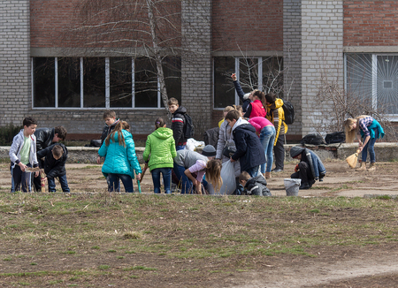 makeevka: Makeevka, Ukraine - March, 26, 2015: Pupils work on landscaping the school grounds during the truce