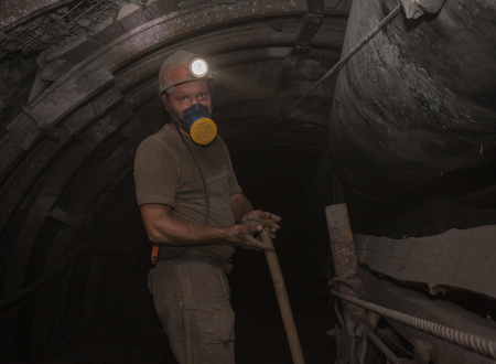 coal mine: Donetsk, Ukraine - March, 14, 2014: The miner working underground in the mine named Abakumov in dusty conditions