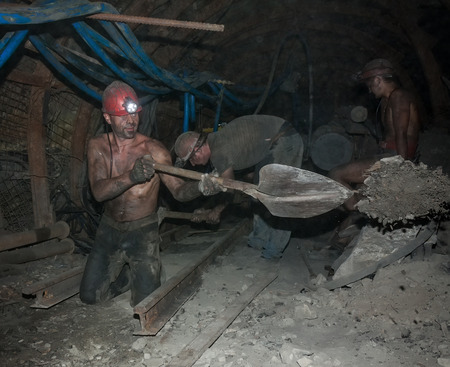 Donetsk, Ukraine - August, 16, 2013: Miners perform heavy manual labor in low light conditions and dusty. Mine is named Chelyuskintsev Editorial