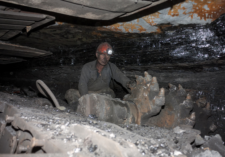shearer: Donetsk, Ukraine - August, 16, 2013: Miner near the coal mining shearer. Mine is named Chelyuskintsev