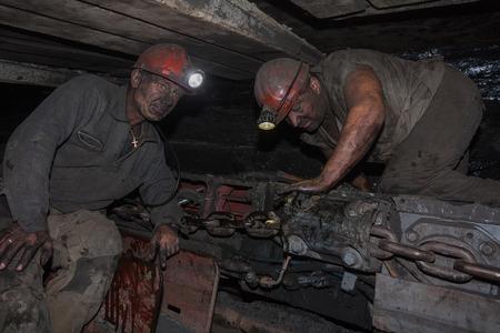 movable: Donetsk, Ukraine - August, 16, 2013: Miners near the coal mining shearer. Mine is named Chelyuskintsev